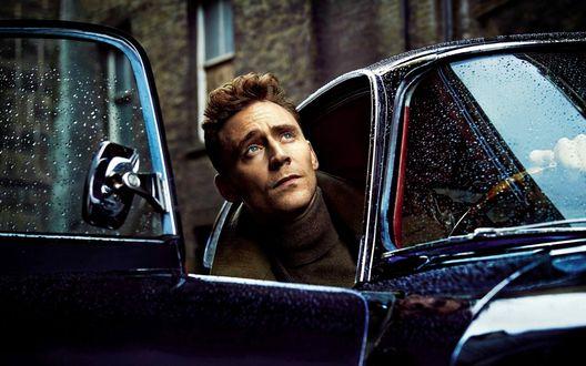 Обои Актер Том Хиддлстон / Tom Hiddleston высунул голову из машины и смотрит вверх