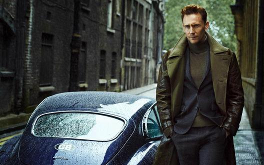 Обои Актер Том Хиддлстон / Tom Hiddleston стоит на улице, рядом с машиной Ягуар / Jaguar