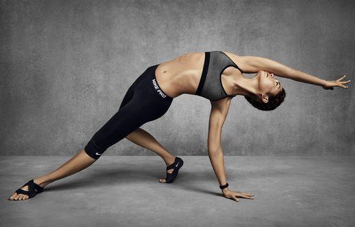 Обои Спортивная девушка стоит в позе из йоги на сером фоне