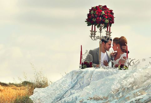 Обои Прекрасная пара влюбленных смотрят друг другу в глаза сидя за столом с белоснежной скатертью на котором находятся свечи и цветы, на фоне поля
