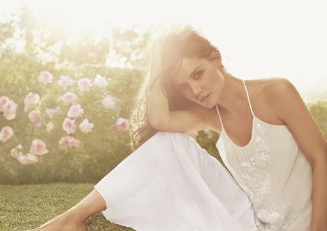 Обои Актриса Кэти Холмс / Katie Holmes в рекламной фотосессии для бренда Ann Taylor в белом платье сидит на зеленой траве на фоне кустов с розовыми цветами