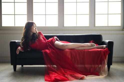Обои Азиатка в красном платье лежит на диване у окна