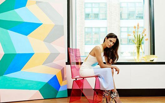 Обои Джордана Брюстер / Jordana Brewster сидит на стуле, в комнате с гомерическим узором на стене