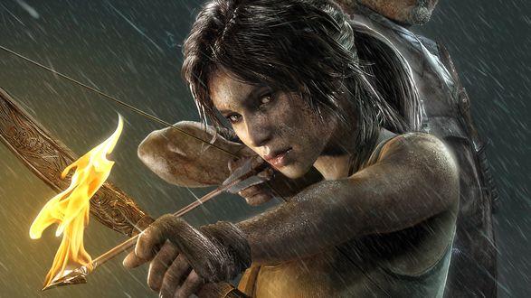 Обои Lara Croft / Лара Крофт - главная героиня знаменитой компьютерной игры Tomb Raider / Томб Райдер / Расхитительница гробниц, стоя рядом с мужчиной к нему спиной, целится из лука, заряженного огненной стрелой, под дождем