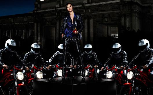 Обои Ольга Куриленко / Olga Kurylenko с коктейлем в руке стоит на помосте, вокруг нее собрались байкеры в шлемах