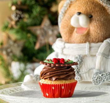 Обои Пирожное с шоколадным кремом на белой тарелке на фоне плюшевого мишки в белой кофточке и новогодней елки с красивыми украшениями