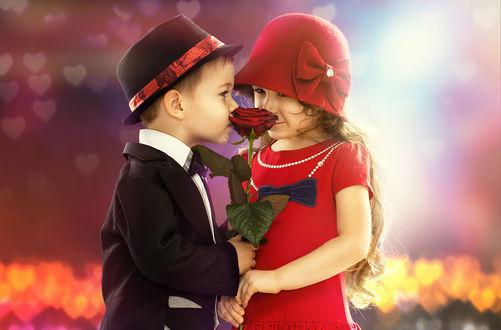 Обои Мальчик в черной шляпе и смокинге дарит девочке в красной шляпке и красном платье розу на фоне сердечек