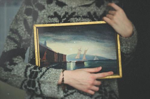 Обои Девушка держит в руках картину