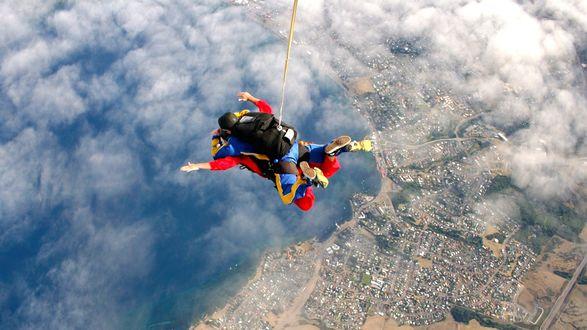 Обои За мгновенье до раскрытия купола парашюта, парашютист парит над облаками и раскинувшимся внизу городом
