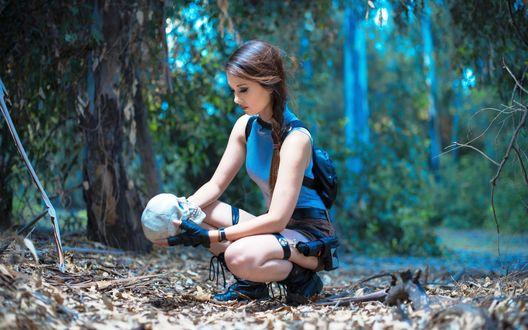Обои Lara Croft / Лара Крофт из игры Расхитительница гробниц / Tomb Raider сидит на корточках, держа в руках человеческий череп, в лесу во время черных раскопок, косплей / cosplay