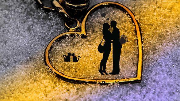 Обои Силуэты влюбленных пар людей и кошек внутри брелка в виде сердечка, лежащего на снегу