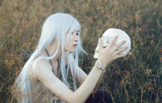 Обои Юноша с длинными белыми волосами внимательно смотрит на череп в своих руках, сидя в траве / Come to the Death by Crimson-Shad