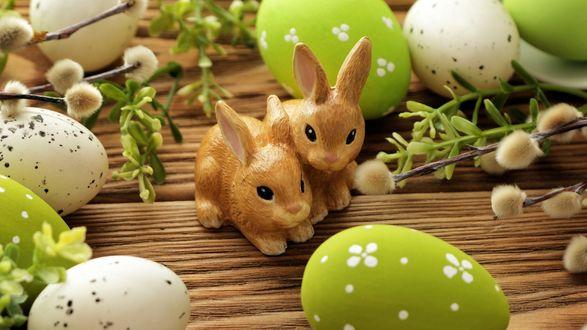 Обои Статуэтки зайцев среди крашеных яиц и веточек вербы на деревянной поверхности, к празднику Светлой Пасхи