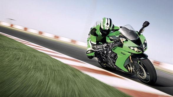 Обои Мотоциклист в зеленых шлеме и комбинезоне, мчится по шоссе на зеленом гоночном мотоцикле