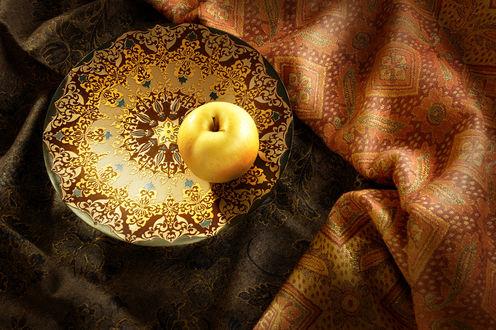 Обои Желтое яблоко, лежащее на красивой, расписанной узорами чаши, находящейся на цветной драпировке