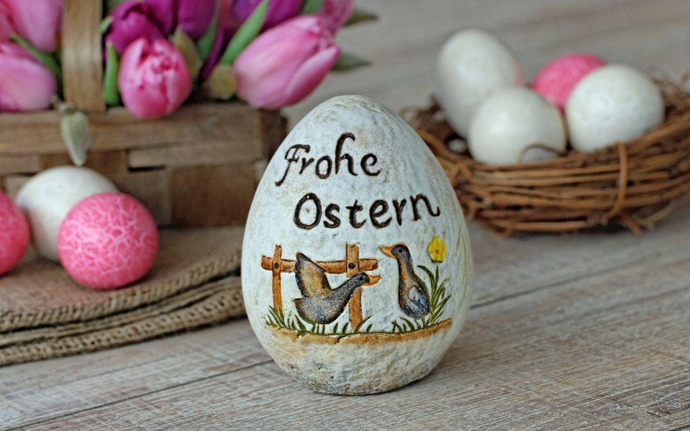 Обои для рабочего стола Большое керамическое пасхальное яйцо с двумя нарисованными утками и надписью Frohe Ostern / Счастливой Пасхи, позади которого обычные пасхальные яйца и розовые тюльпаны
