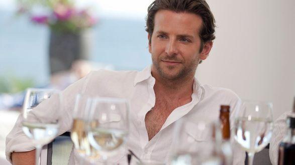 Обои Красивый мужчина сидит за столом, на столе бокалы и вино, актер bradley cooper