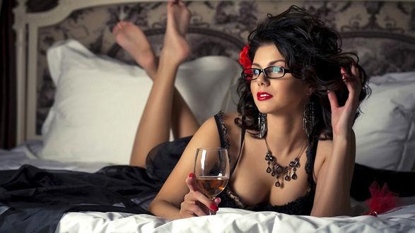 Обои Красивая девушка лежит на кровати с бокалом вина в руке и теребит волосы