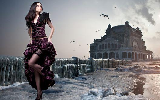 Обои Стройная девушка стоит на обледеневшем мосту, который ведет в полуразрушенный замок