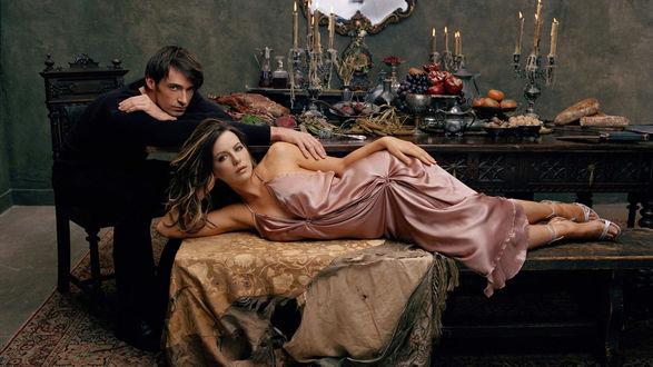 Обои Девушка лежит на скамье, покрытой покрывалом, рядом сидит парень, оба смотрят на нас, на заднем плане стол, накрытый явствами, кадр из кинофильма Ван Хельсинг