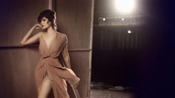 Обои Грустная девушка в легком бежевом платье стоит на фоне стены, подперев щеку рукой
