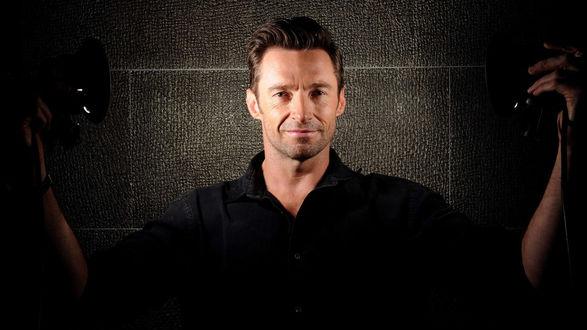 Обои Красивый мужчина стоит на фоне стены, держа в руках осветительные приборы, актер Hugh Jackman (Хью Джекман)