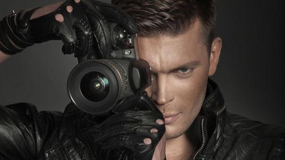 Обои Красивый парень в черной кожанной куртке и перчатках, держит фотоаппарат, направленный на нас