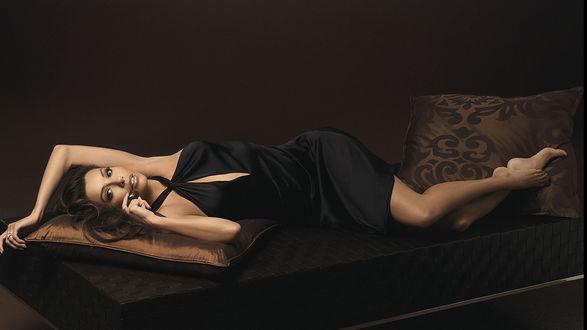 Обои Брюнетка в черном платье лежит на софе, положив голову и ножки на подушки, актриса Ева Лонгория