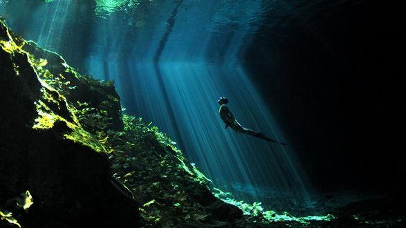 Обои Пловец поднимается на поверхность воды в чистейшем озере, солнечные лучи пробиваются сквозь воду