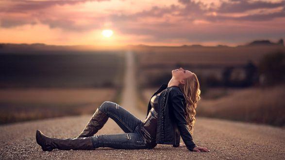 Обои Девушка сидит на пустынной дороге и смотрит вверх, солнце садится за горизонт