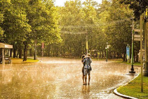 Обои Влюбленная пара целуется под дождем, стоя прямо посреди дороги