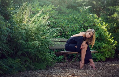 Обои Светловолосая девушка в синем платье, сидит на скамейке в живописном месте, глядя на нас