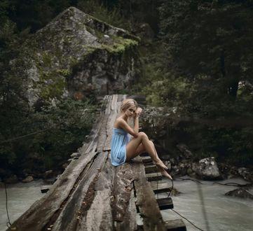 Обои Грустная девушка в голубом платье сидит на старом мосту над горной рекой и смотрит на нас