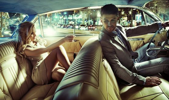Обои Мужчина и девушка едут в машине по городским улицам, мужчина оглядывается на спутницу