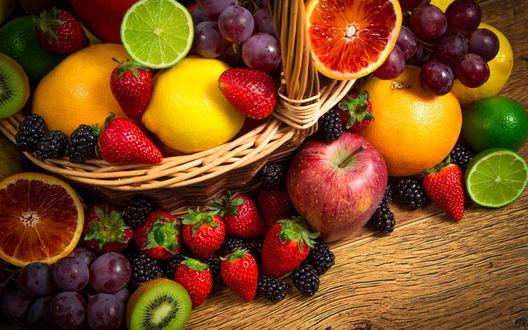 Обои В корзинке и на столе лежат виноград, клубника, ежевика, лимон, апельсины, яблоки, лимон лайм, киви