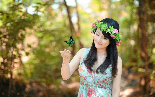Обои Девушка в венке из цветов с большой яркой бабочкой зависшей у руки, на фоне деревьев