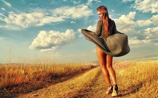 Обои Сильный порыв ветра взметнул подол платья русоволосой девушки, на поле, на фоне неба и облаков