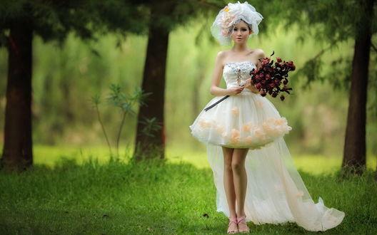 Обои Азиатка в коротком свадебном платье с фатой и букетом розирует на фоне деревьев в парке