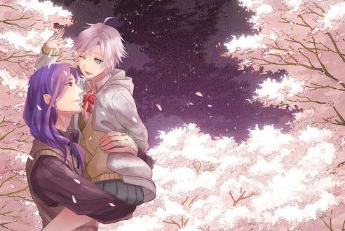 Обои Парень держит девушку на руках на фоне весенних деревьев