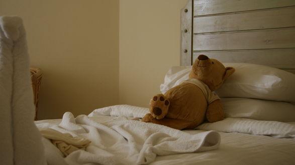 Обои Игрушечный медведь лежит на кровати, закинув ногу на ногу