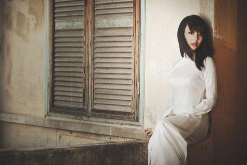 Обои Девушка азиатка сидит в белом платье на выступе, у старого окна