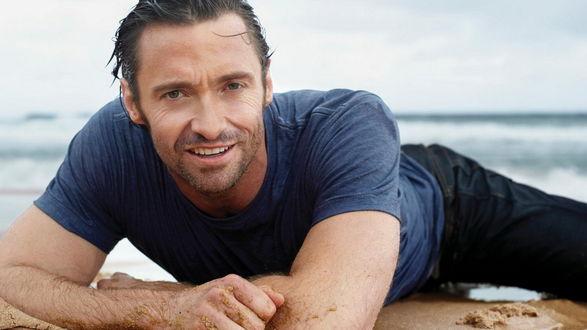 Обои Актер Хью Джекман лежит на песке на берегу моря и смотрит на нас