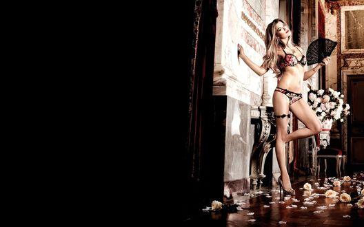 Обои Длинноволосая, длинноногая девушка в туфлях и в красивом нижнем белье с веером в руках стоит в комнате, пол которой усыпан розами