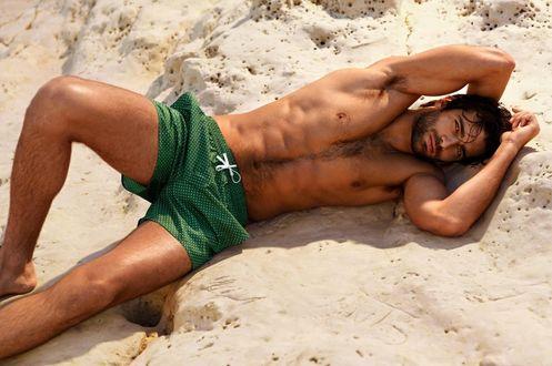 Обои Мужчина в зеленых шортах лежит на солнечном пляже