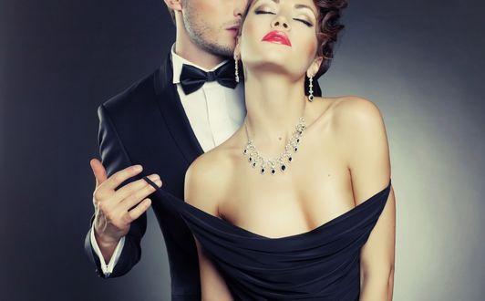 Обои Мужчина целует женщину, стоя у нее за спиной и стягивая лямку платья