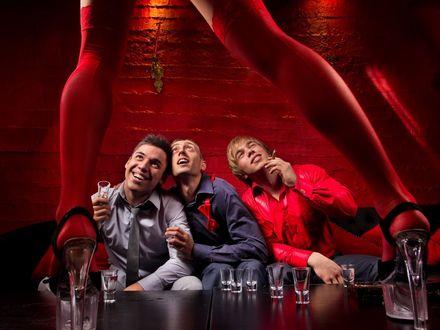 Обои Парни на мальчишнике, на столе стоит девушка в красных чулках и туфлях, парни выпивают и курят