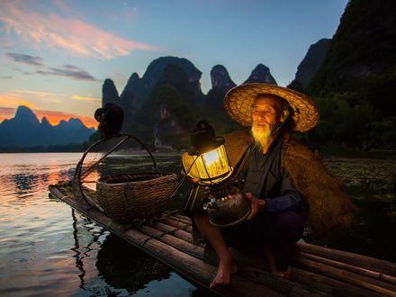 Обои Старик китаец ранним утром ловит рыбу, сидя на плоту, подсвечивая себе лампой