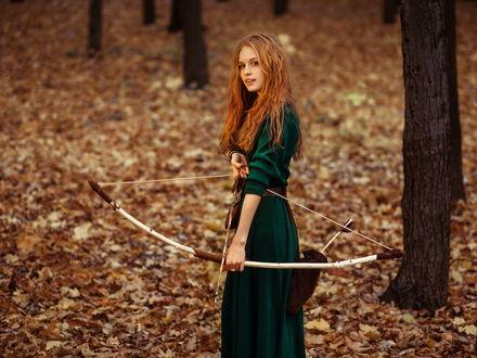 Обои Красивая рыжеволосая девушка стои посреди осеннего леса, в руках у нее лук со стрелой