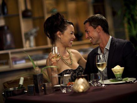 Обои Мужчина и женщина смеются, сидя за столиком ресторана