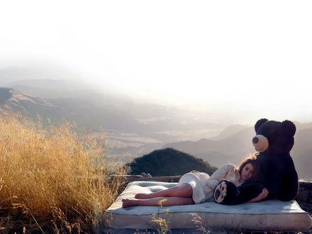 Обои Девушка лежит на матрасе, обнимая большого плюшевого медведя, вокруг красивый утренний пейзаж